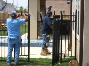 wrought iron gate being installed in sugar land