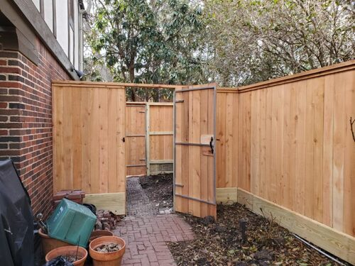 wood fence with an open door league in league city