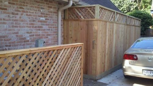 wood fence on the side of a home in the woodlands