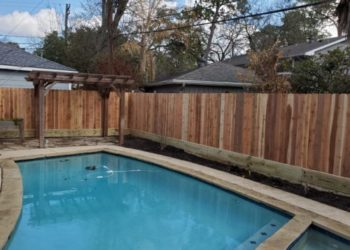 wood fence being installed around a swimming pool